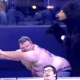 A man cheering up his home team in ice hockey with his bizarre dance skills