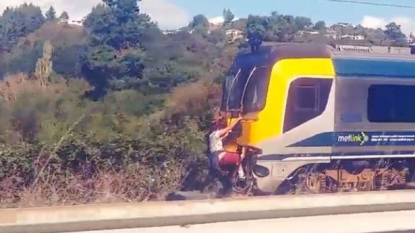 Two men risked their lives by hanging at the back of high speed train