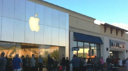 Robot waits in line for iPhone in woman's place
